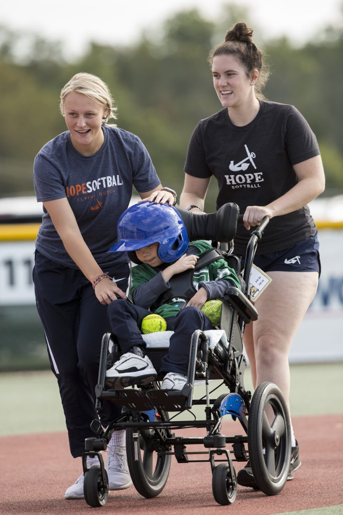 Hope players help a WMML player in a wheelchair field a ball