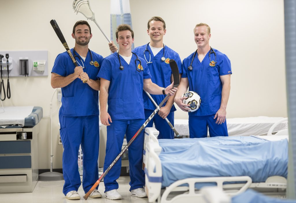 Trace Slancik, Austin Kane, Nick Bazany, and Blair McCormick pose for a portrait in a hospital room.