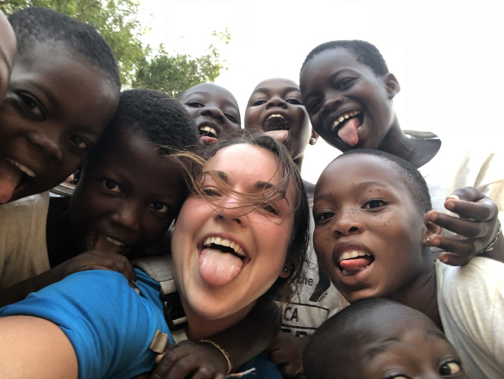 Megan Bigelow takes a selfie photo with eight children from Ghana.