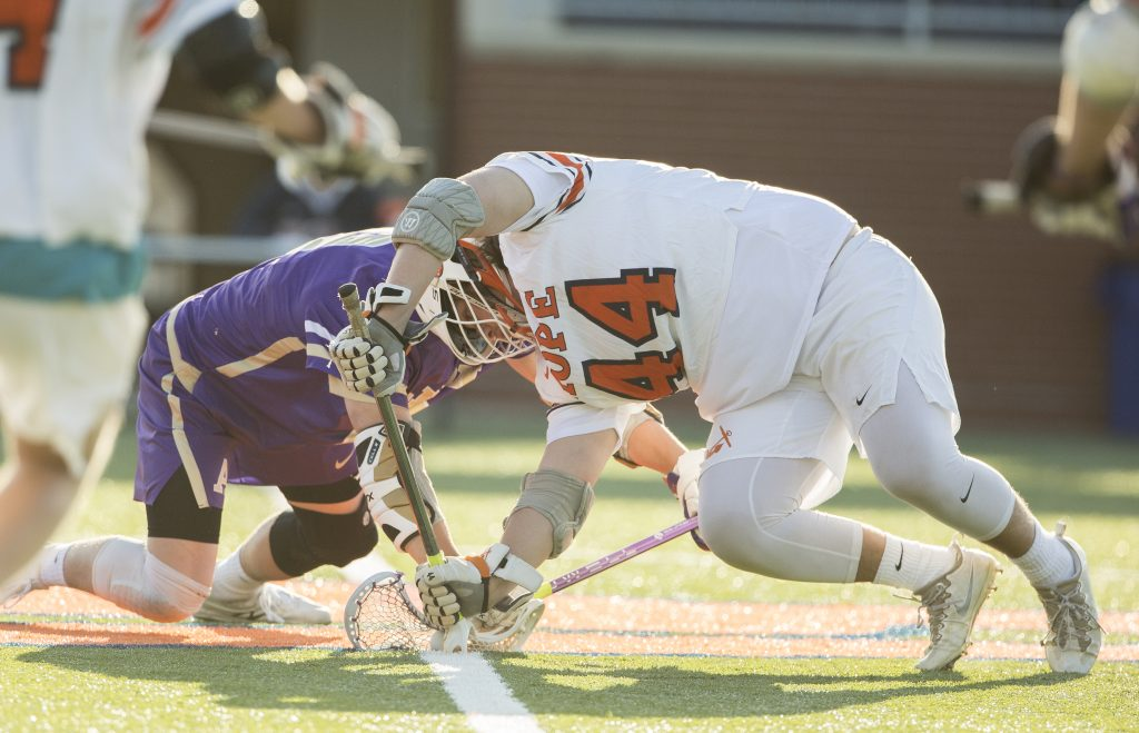 Cole Sheffler engaged in a face-off in lacrosse