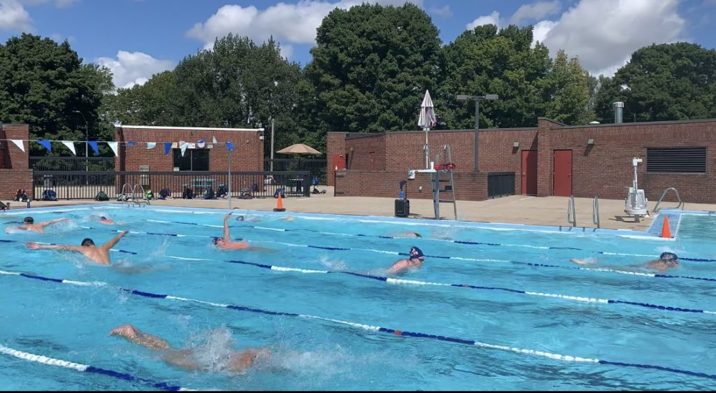 Hope College swimmers, in multiple lanes, train outdoors at the City of Holland Bouws Pool.