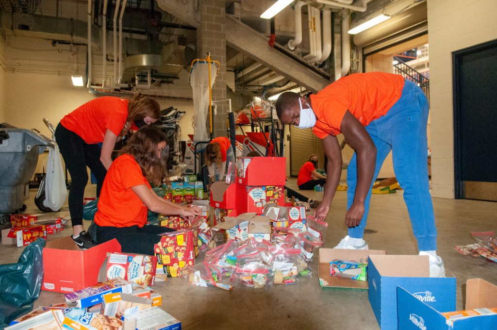 Five Hope College student-athletes pack granola bars, crackers, apple sauce and fruit snacks in a Ziploc bags at DeVos Fieldhouse.