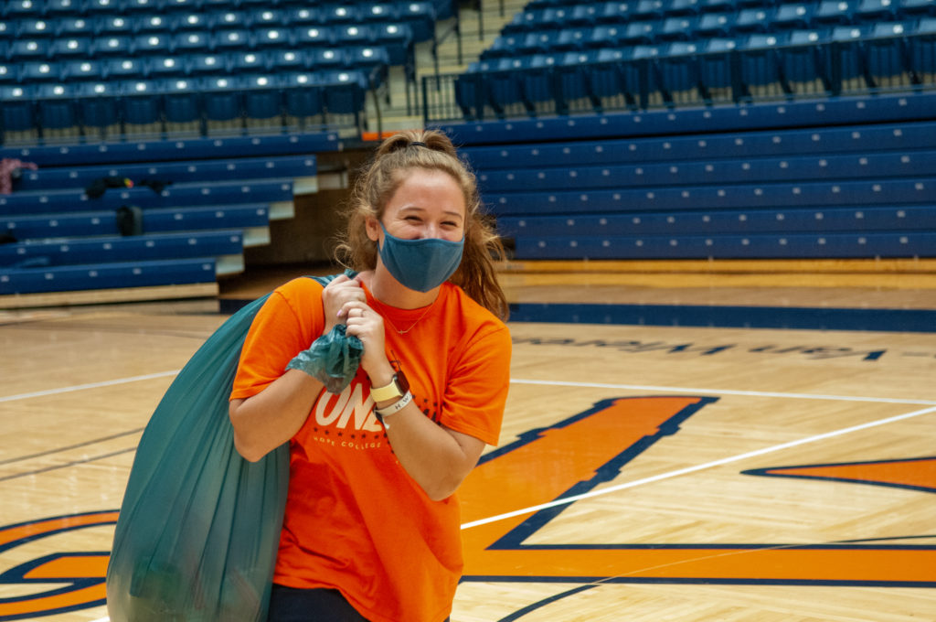 A Hope student-athletes carries a bag of snack packs to the loading dock at DeVos Fieldhouse.
