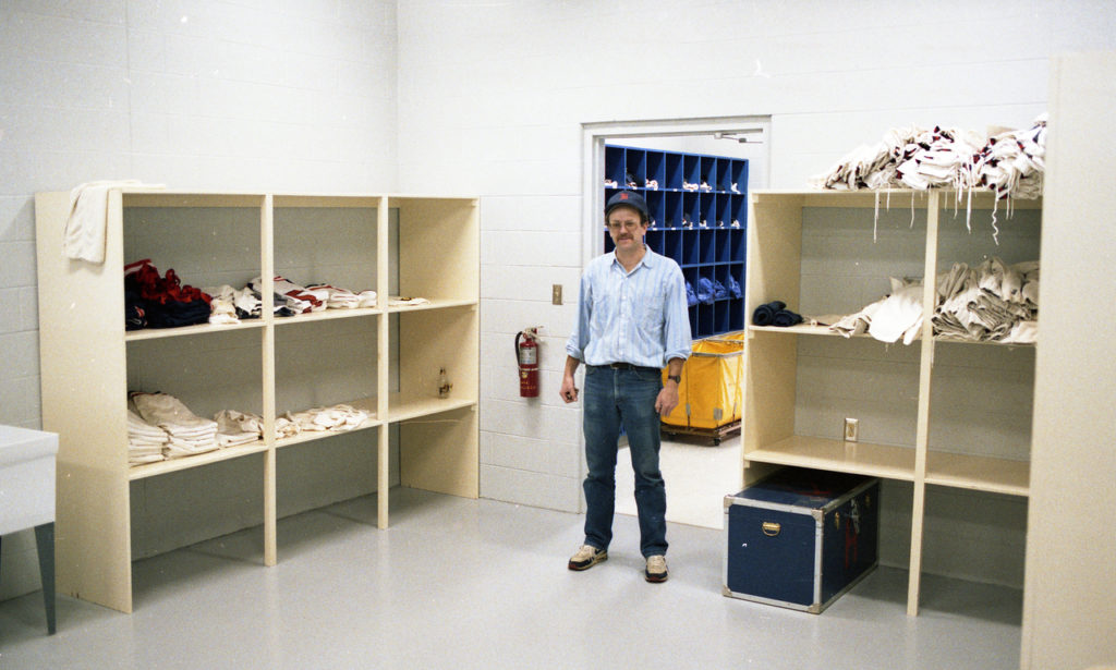 Equipment manager Gordon VanderYacht stands inside a white storage room between two shelves.
