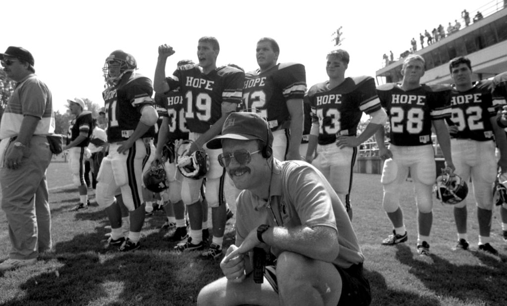 Equipment manager Gordon VanderYacht kneels in front of Hope football players on the sideline during a game.