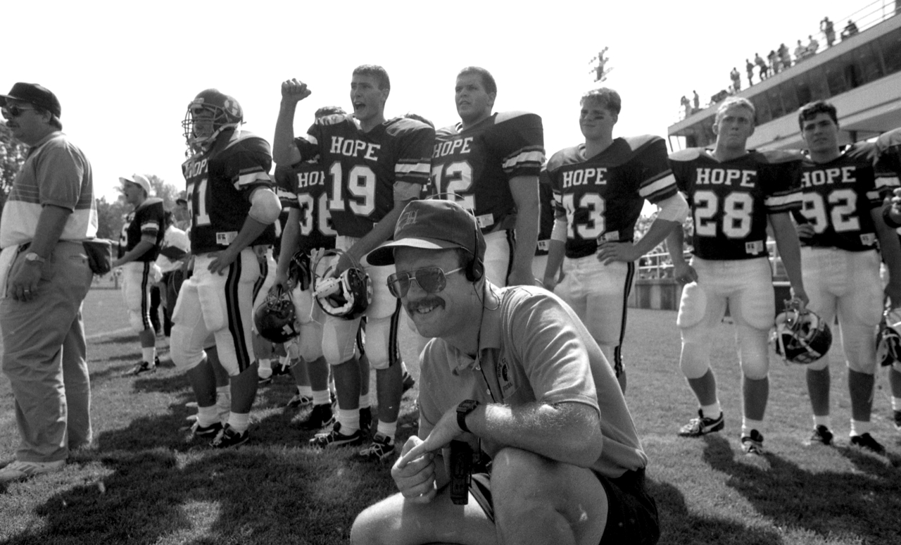 Gordon VanderYacht kneels in front of Hope football players on the sideline during a game.