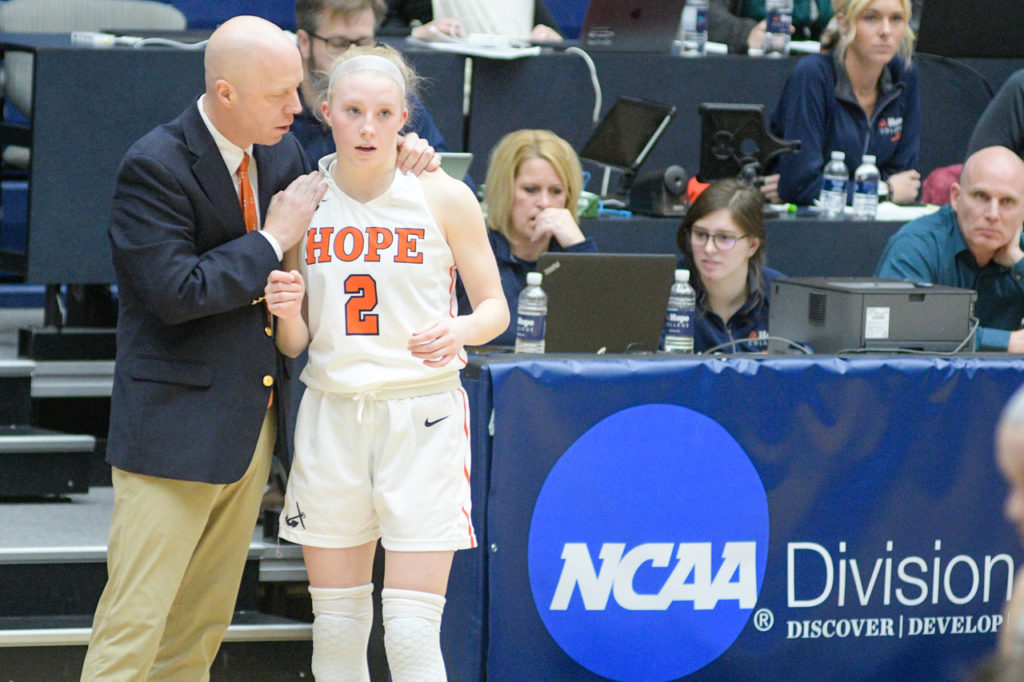 Brian Morehouse and Meg Morehouse huddle during a basketball game at DeVos Fieldhouse.