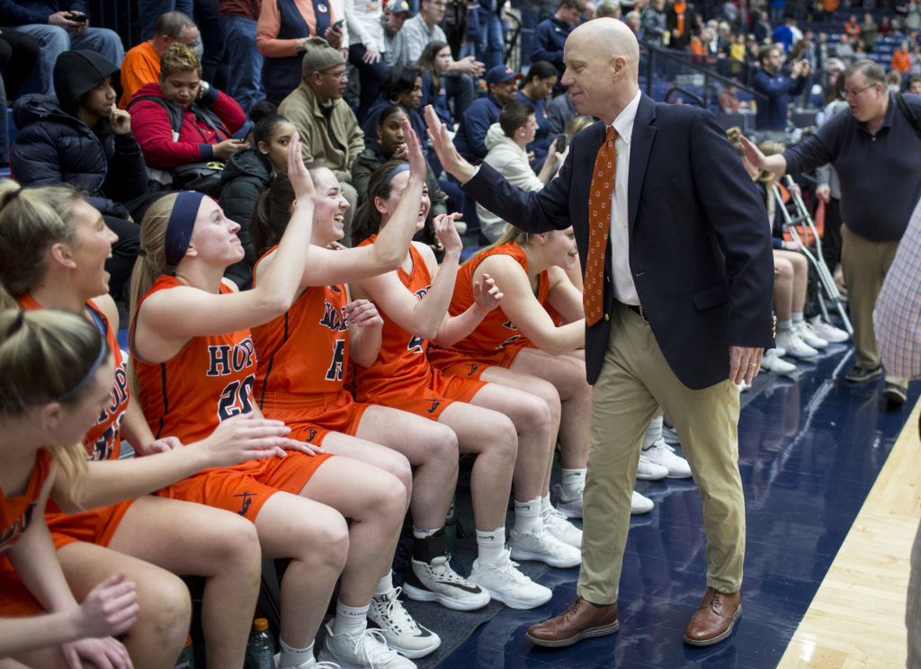 Hope College women's basketball coach Brian Morehouse exchanges high-fives on the bench at DeVos Fieldhouse during a 2020 MIAA Tournament game.