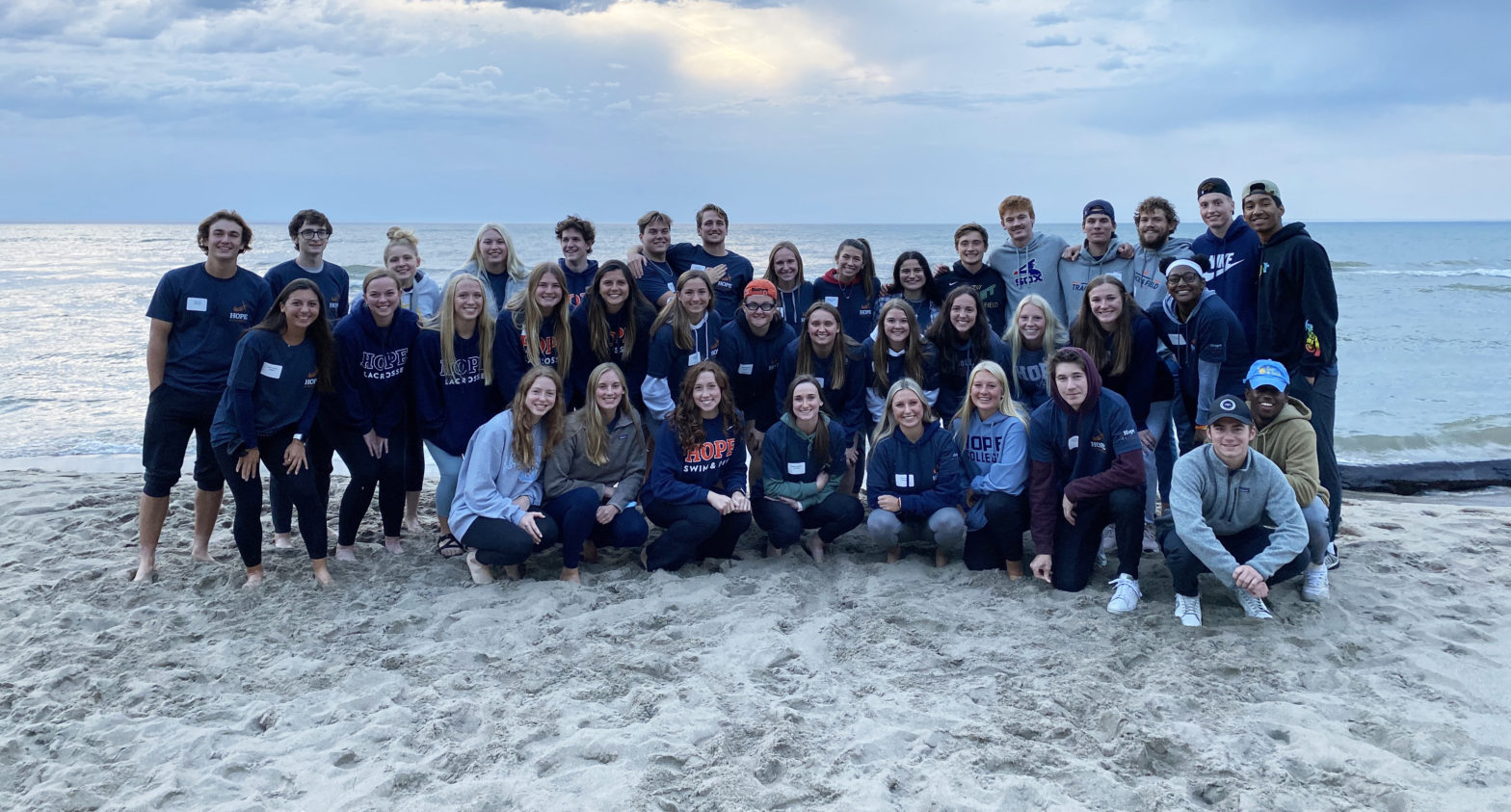 40 Hope student-athletes poses for a group photo on the shores of Lake Michigan.