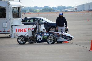 Hope student, YYYY YYY ('XX), seated in the Hope FSAE car in full race gear prepared to begin an autocross course.