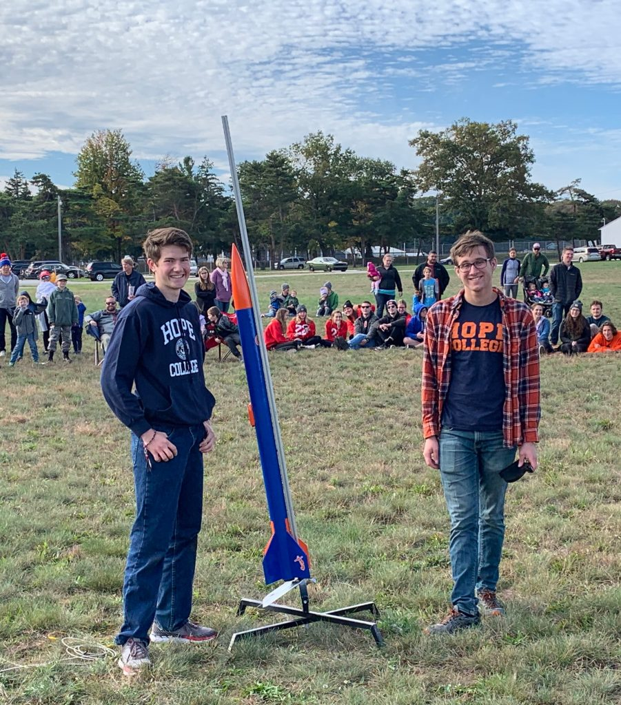Hope students smiling next to 5 foot rocket in blue and orange Hope colors