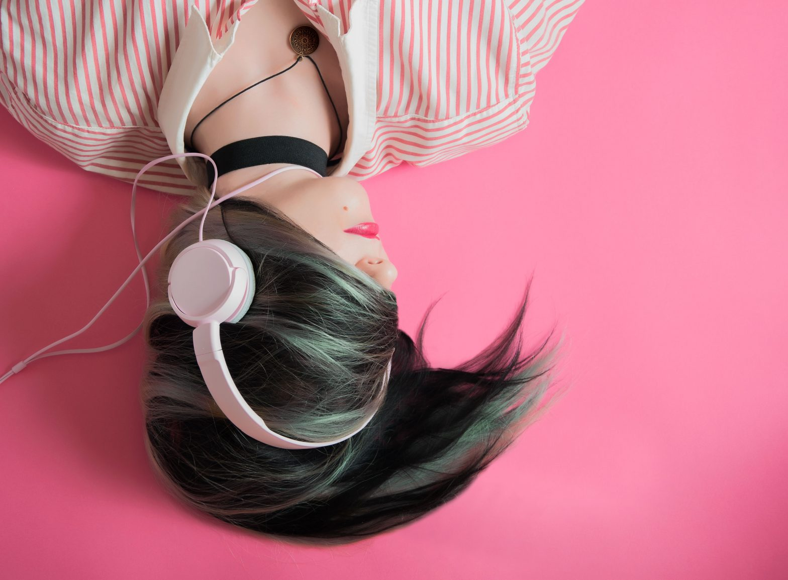 Upside-down image of a woman with green hair listening to headphones.