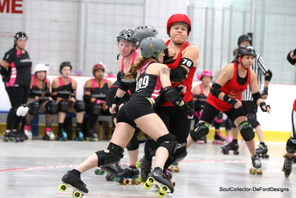 Brenna taking on an opponent in roller derby.