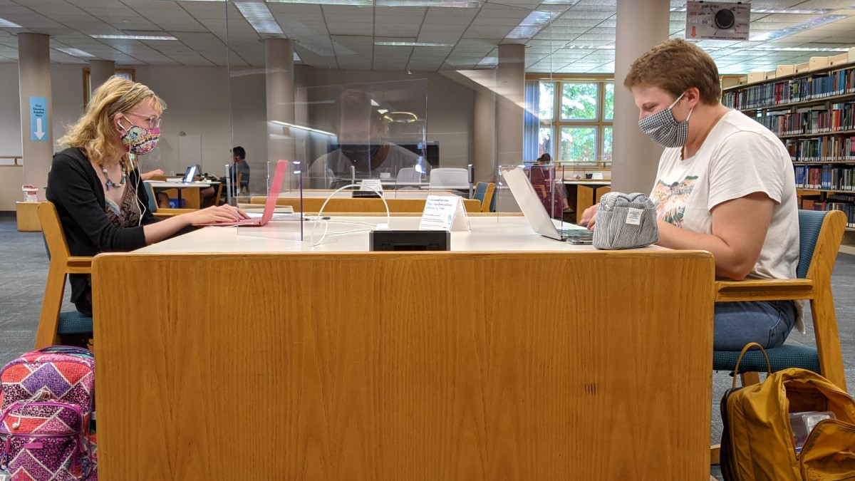 Two students sitting at a table in the library and maintaining a distance of six feet