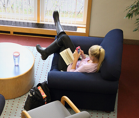 A student relaxing in the A.J. Muste Alcove