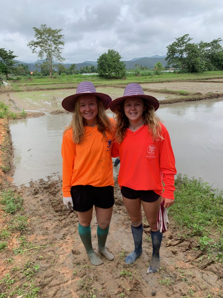 "My friend Kayli and I after attempting to use the ""iron buffalo"" to plow the rice field.  Walking in the fields is much harder than it looks, as you sink into a foot of mud with every step."