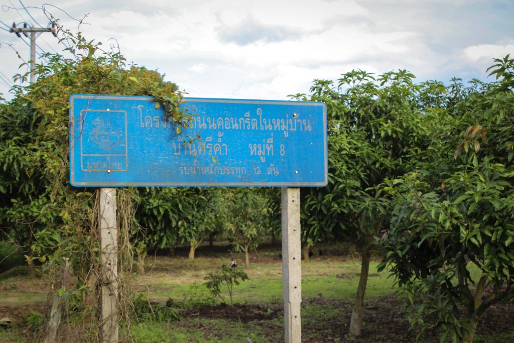 Sign by one of the orchards in Sri Kham Village giving weight limits for the concrete roads.