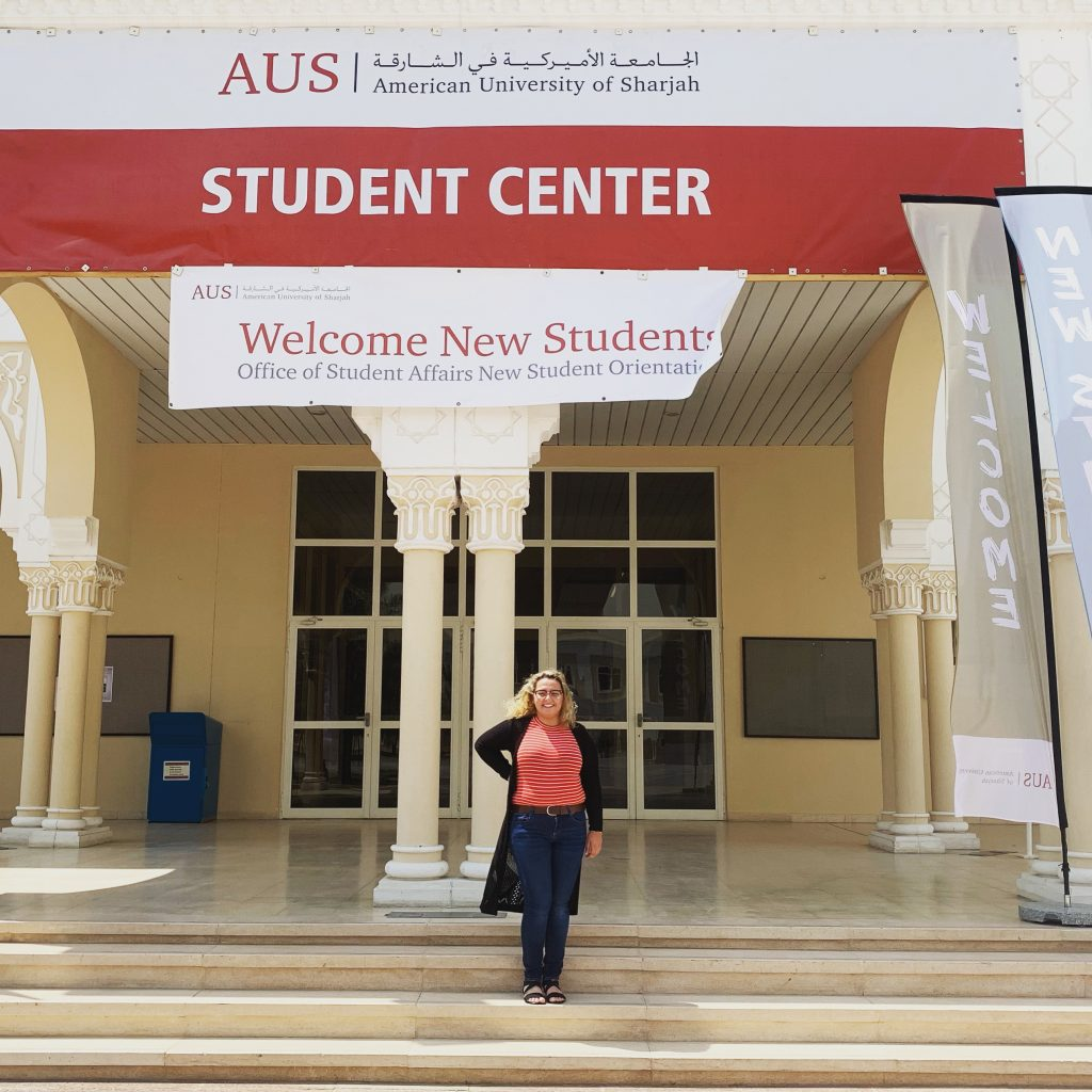 "Safia is standing on the steps of the Student Center at the American University os Sharjah. Above her head, a banner reads ""Welcome New Students"". Safia ia wearing a red shirt with white stripes, jeans, and a black cardigan and is smiling"
