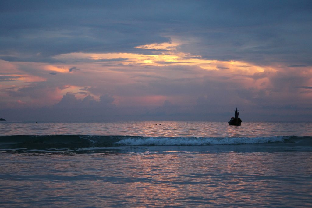 Off in the distance you see a small boat, the view of the colorful clouds as the sun sets, and the waves hitting shore