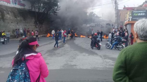 A newspaper photo of some of the protests in Quito showing burning tires blocking a road