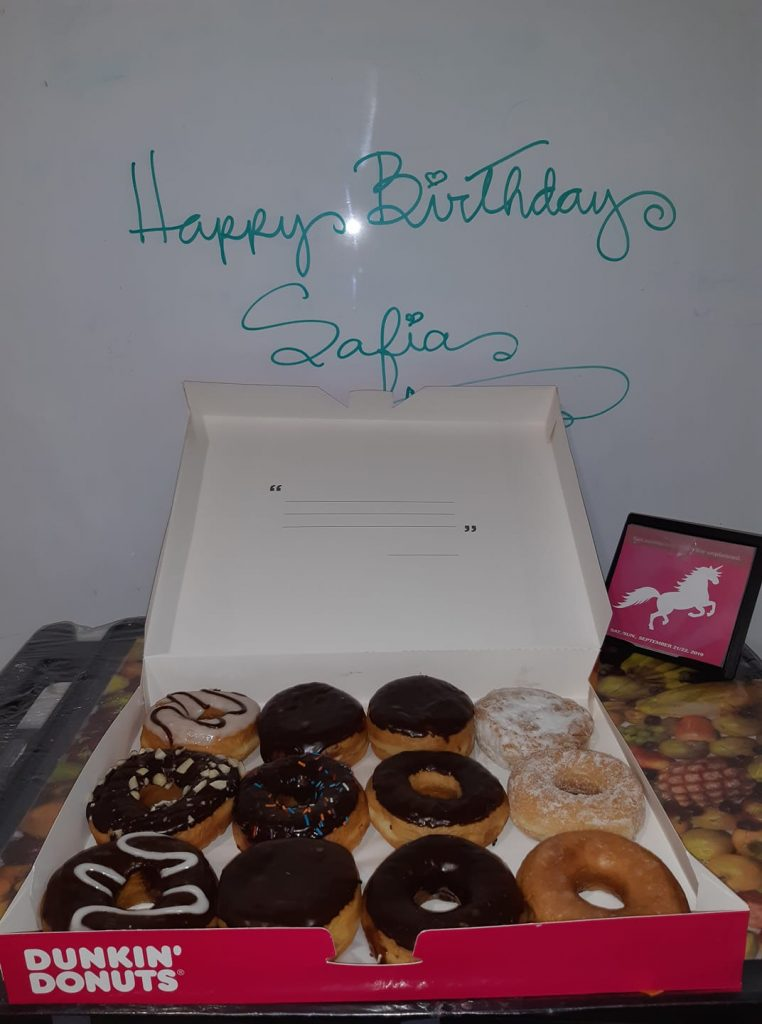"An open box of a dozen Dunkin Donuts donuts sitting on a table with the words, ""Happy Birthday Safia"" written in green cursive on the white board behind it."