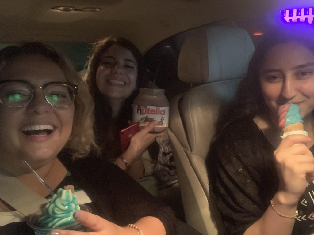 From left to right: Myself, Houda, and Nasreen each holding a different ice cream. Houda's is in a Nutella jar. We are seating in Nasreen's car, all smiling at the camera.
