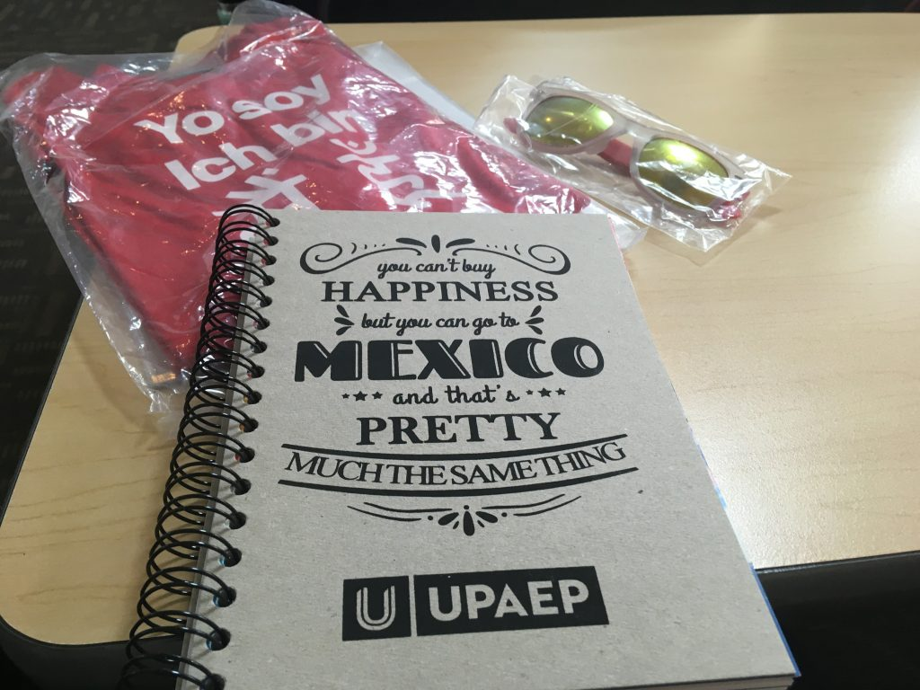"Gifts from UPAEP: ""I AM UPAEP"" t-shirt, sunglasses, and a cute notebook"