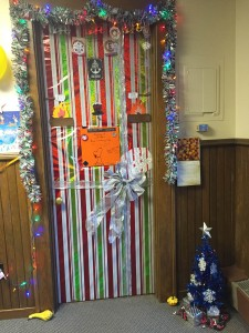 Door decorated with wrapping paper and a little blue Christmas Tree