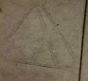 The Hope College Anchor logo imprinted in the cement of the sidewalk
