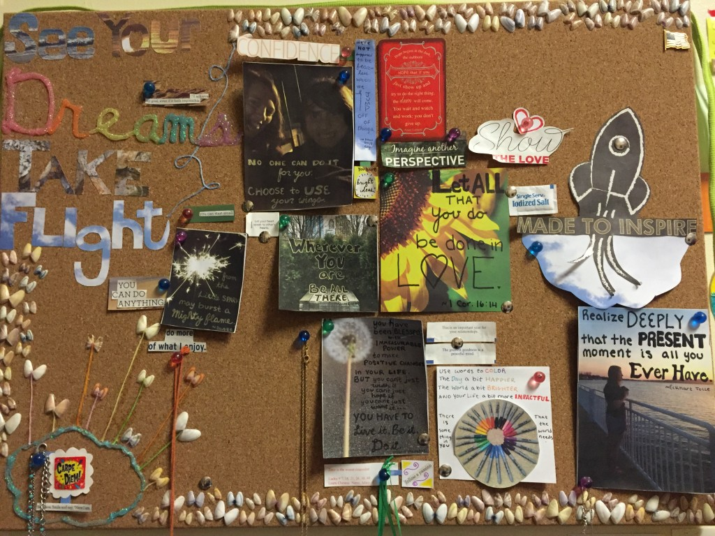 Bulletin board lined with little shells with pictures and quotations pinned to it.