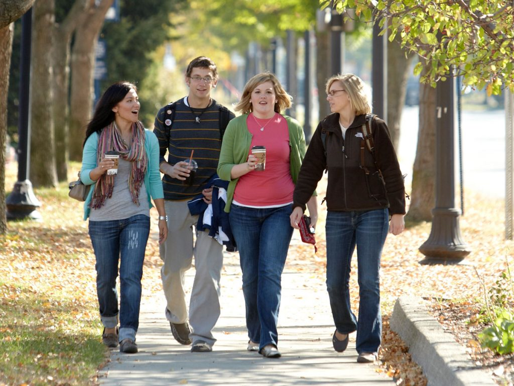 Four students walking on sidewalk under trees.