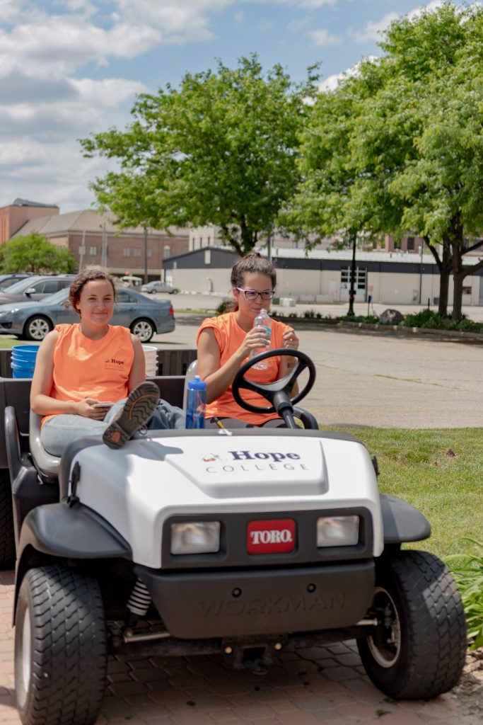 Student workers for physical plant driving a utility vehicle.
