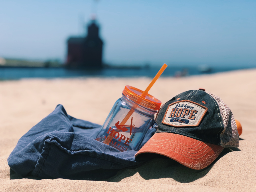 hope hat and water bottle in foreground, shadow of big red lighthouse in background