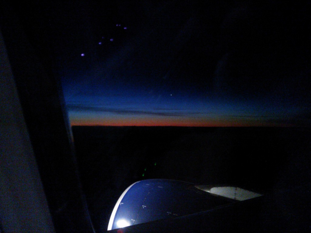 Sunrise as viewed from the plane - although my cellphone pic doesn't do it justice. The blue cylinder at the bottom is the jet engine sticking out beneath the wing.